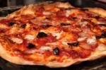 Knusprig dünn: Pizza mit Büffelmozzarella, gebackenen Oliven und Spinata aus Kalabrien